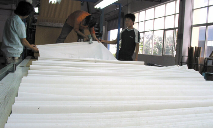 Shenzhen, China:  Workers view the production of paper at a paper mill in the southern Chinese city of Shenzhen on 19 Oct. 2006. (Peter Harmsen/AFP via Getty Images)