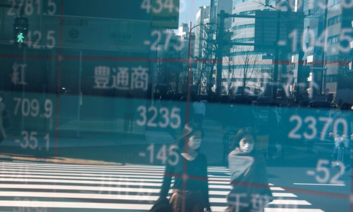 People are reflected on a screen showing Nikkei index, outside a brokerage in Tokyo, Japan, on Feb. 28, 2020. (Athit Perawongmetha/Reuters)