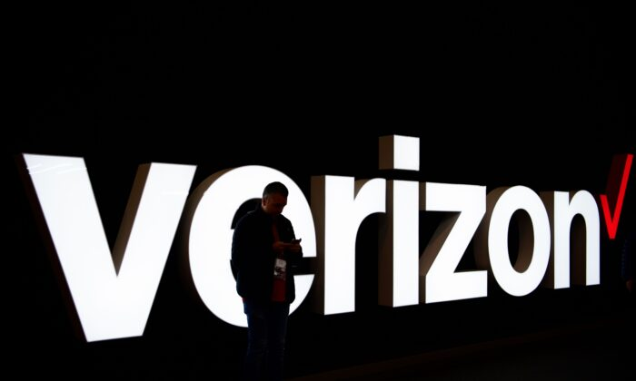 A man stands in front of the Verizon logo at the Mobile World Congress (MWC) in Barcelona on Feb. 25, 2019. (Gabriel Bouys/AFP via Getty Images)