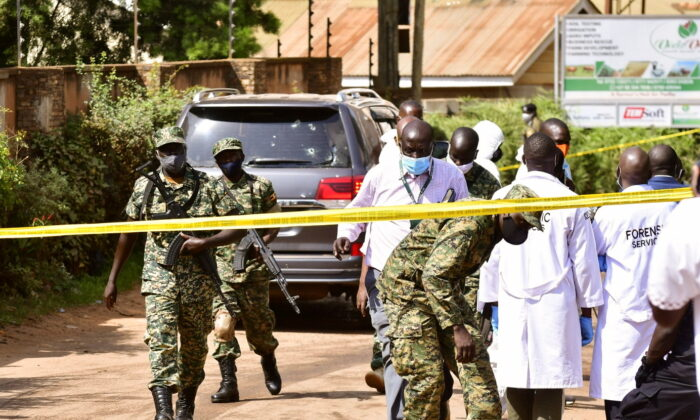 Security forces and forensic experts secure the scene of an attempted assassination on Ugandan minister of works and transport General Katumba Wamala in the suburb of Kiasasi within Kampala, Uganda, on June 1, 2021. (Abubaker Lubowa/Reuters)