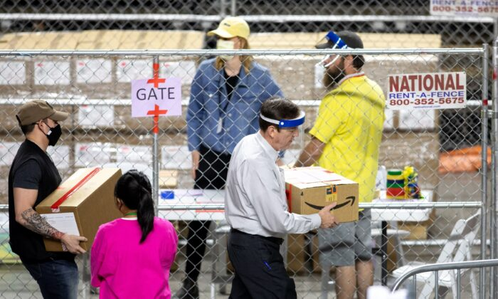 Former Arizona Secretary of State Ken Bennett, right, works with others to move ballots from the 2020 general election during an audit at Veterans Memorial Coliseum in Phoenix, Ariz., on May 1, 2021. (Courtney Pedroza/Getty Images)