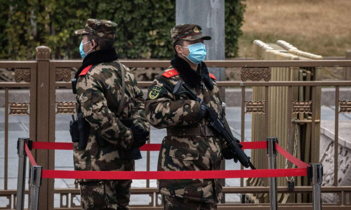 Chinese soldiers stand guard on a street intersection in Beijing, on March 3, 2021. (Nicolas Asfouri/AFP via Getty Images)