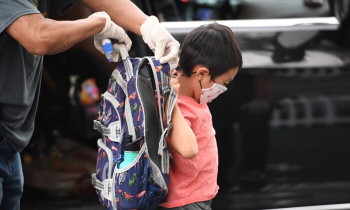 A staff member helps a student put on his backpack at STAR Eco Station Tutoring & Enrichment Center in Culver City, Calif., on Sept. 10, 2020. (Robyn Beck/AFP via Getty Images)