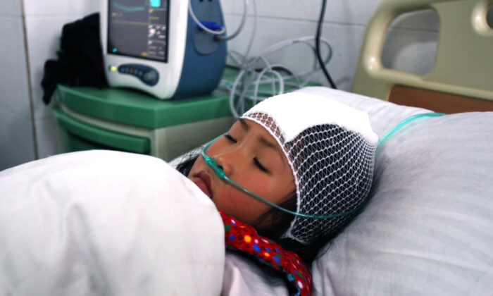 A girl lies on a hospital bed after she was stabbed during a knife attack at a primary school in Guangshan county, central China's Henan Province on Dec. 16, 2012. (STR/AFP via Getty Images)
