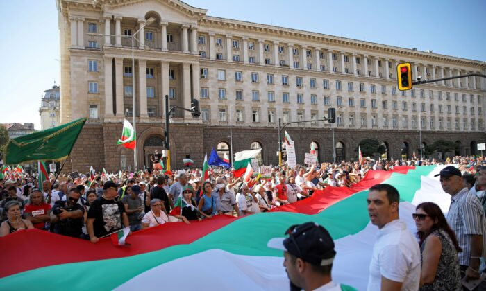 Protesters hold a large Bulgarian flag as they attend an anti-government demonstration in Sofia, Bulgaria, on Sept.10, 2020. (Stoyan Nenov/Reuters)