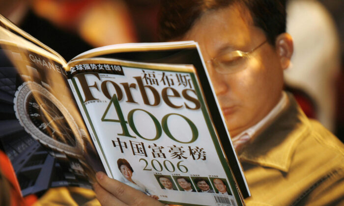 A journalist reads the latest copy of Forbes magazine at a press conference to announce the magazine's list of China's 400 wealthiest people in Beijing on Nov. 2, 2006. (Peter Parks/AFP via Getty Images)