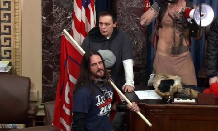In this image from closed circuit television footage, a man identified as Paul Hodgkins, front, holds a flag while in the Senate chamber inside the U.S. Capitol in Washington on Jan. 6, 2021. (CCTV via FBI)