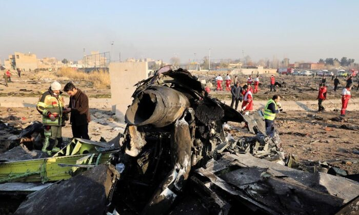 Debris is seen from an Ukrainian plane which crashed as authorities work at the scene in Shahedshahr, southwest of the capital Tehran, Iran on Jan. 8, 2020. (The Associated Press/Ebrahim Noroozi)