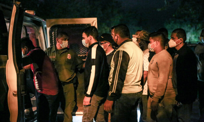 Border Patrol agents detain illegal immigrants after they cross the Rio Grande from Mexico into Del Rio, Texas, on May 23, 2021. (Charlotte Cuthbertson/The Epoch Times)