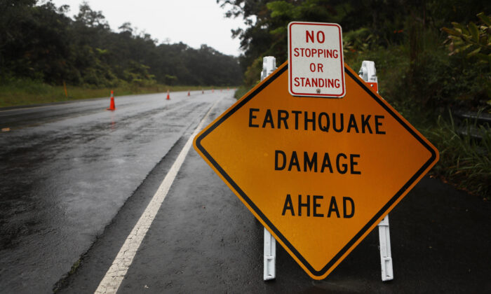 A sign is posted warning of earthquake damage to the road from seismic activity at the Kilauea volcano on Hawaii's Big Island on May 17, 2018 in Hawaii Volcanoes National Park, Hawaii. (Mario Tama/Getty Images)