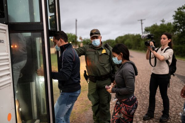 Migrants board a bus