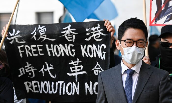 """Hong Kong democracy activist Nathan Law stands next to a banner reading """"Free Hong Kong. Revolution now"""" as he attends a demonstration outside the Foreign Office in Berlin, Germany, on Sept. 1, 2020. (Tobias Schwarz/AFP via Getty Images)"""