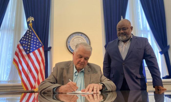 Nevada Gov. Steve Sisolak signs bill to expand voting access on June 2 alongside state Assembly Speaker Jason Frierson. (Courtesy of Governor Steve Sisolak's office)