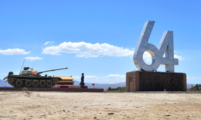 """A life-size sculpture of """"Tank Man"""" stands beside the numbers """"6"""" and """"4,"""" representing June 4, and a miniature sculpture of Tiananmen Rostrum, on display at Liberty Sculpture Park in the Mojave desert town of Yermo, Calif., on June 1, 2021. (Frederic J. Brown/AFP via Getty Images)"""