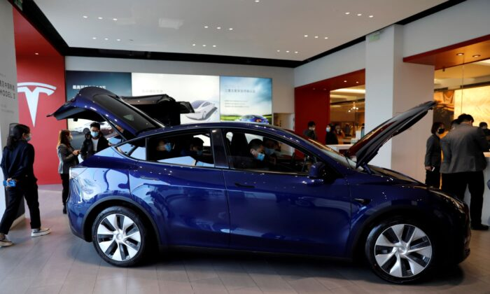 Visitors check a China-made Tesla Model Y sport utility vehicle at the electric vehicle maker's showroom in Beijing on Jan. 5, 2021. (Tingshu Wang/Reuters)