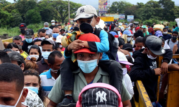 People wearing protective face masks line up to cross the border between Colombia and Venezuela at Simon Bolivar international bridge in Cucuta, Colombia on March 12, 2020. (REUTERS/Carlos Eduardo Ramirez/File Photo)