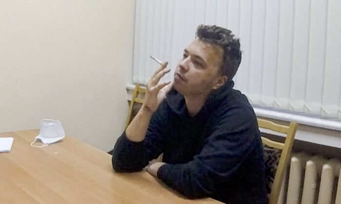 In this handout file photo released by ONT channel dissident journalist Roman Protasevich smokes a cigarette while speaking in a video from a detention center in Minsk, Belarus on Wednesday, June 2, 2021. (ONT channel VIA AP)