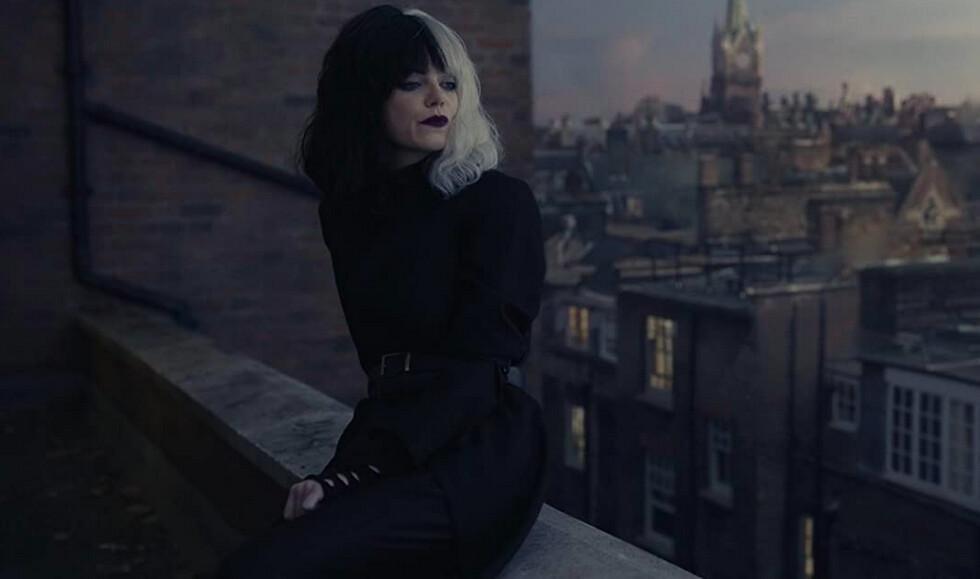 woman sits on balcony in Cruella