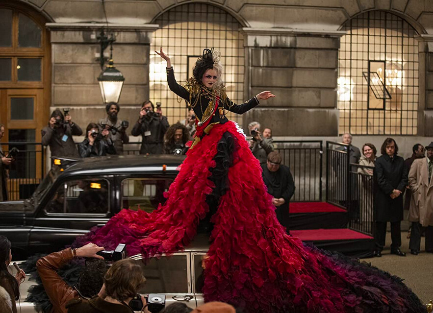 woman in long red gown standing on car in Cruella