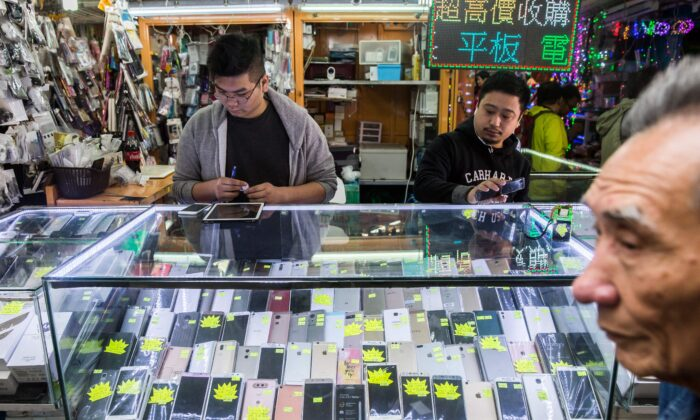 Workers in a secondhand mobile phone store in the Sham Shui Po district of Hong Kong on Jan. 13, 2017. (Isaac Lawrence/ AFP via Getty Images)