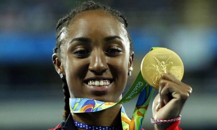 Gold medal winner Brianna Rollins from the United States shows off her medal during the medal ceremony for the women's 100-meter hurdles final during the athletics competitions of the 2016 Summer Olympics at the Olympic stadium in Rio de Janeiro, Brazil, on Aug. 18, 2016. (Dmitri Lovetsky/AP Photo)