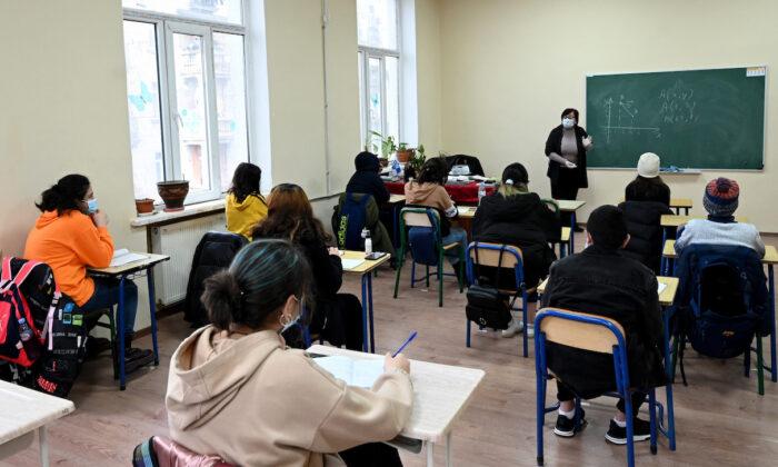 Schoolchildren wearing face masks listen to a teacher at a school in Tbilisi, Georgia on Feb. 15, 2021. (Photo by Vano Shlamov / AFP) (Photo by VANO SHLAMOV/AFP via Getty Images)