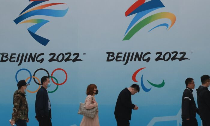 People wear protective masks as they walk in front the logos of the 2022 Beijing Winter Olympics at National Aquatics Centre in Beijing, China, on April 9, 2021. (Lintao Zhang/Getty Images)