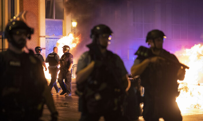 Police stand guard after protesters set fire to dumpsters in Minneapolis, Minn., on June 5, 2021. (Christian Monterrosa/AP Photo)