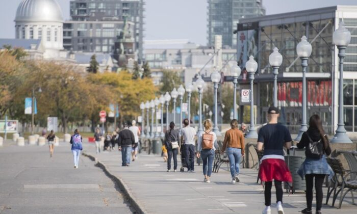 People walk along the promenade in the Old Port in Montreal, on Oct. 10, 2020. (The Canadian Press/Graham Hughes)