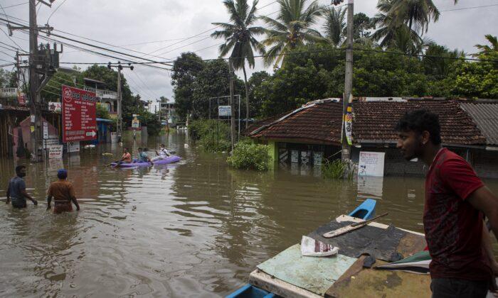 Sri Lankans stranded due to floods travel in a boat in an inundated street following heavy rainfall at Malwana, on the outskirts of Colombo, Sri Lanka, on June 5, 2021. (Eranga Jayawardena/AP Photo)