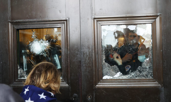 Capitol police officer looks out of a broken window as a crowd attempts to breach the U.S. Capitol, in Washington on Jan. 6, 2021. (Tasos Katopodis/Getty Images)