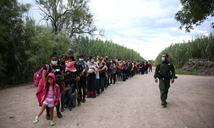 A group of Venezuelans waits to be picked up by Border Patrol after illegally crossing the Rio Grande from Mexico into Del Rio, Texas, on June 3, 2021. (Charlotte Cuthbertson/The Epoch Times)
