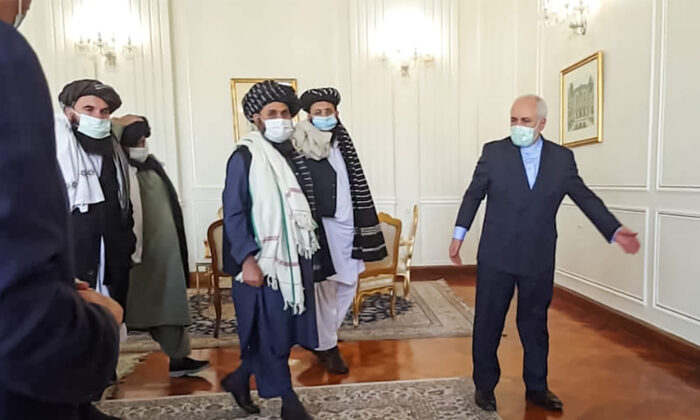 """A picture obtained by AFP from the Iranian news agency Tasnim on Jan. 31, 2021, shows  Iran' Foreign Minister Mohammad Javad Zarif (R) meeting with Mullah Abdul Ghani Baradar (C-L) of the Taliban in Tehran. Iran's Foreign Minister Mohammad Javad Zarif called for the formation of an """"all-inclusive"""" Afghan government during a meeting with a Taliban delegation in Tehran. (TASNIM NEWS/AFP via Getty Images)"""