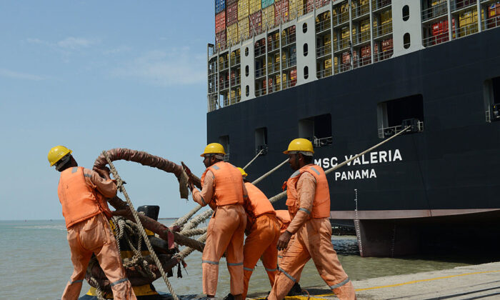 Indian dock workers tighten ropes as the MSC Valeria, an ultra-large containership from the Mediterranean Shipping Company S. A., of Geneva,  docks at Adani Ports at Mundra, some 400 km from Ahmedabad on June 4, 2013.(Sam Panthaky/AFP via Getty Images)