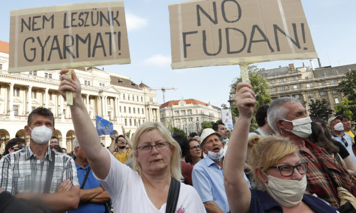 Protesters hold placards reading in Hungarian 'we will not be a colony' (L), and 'no Fudan' as they gather in downtown Budapest, Hungary, on June 5, 2021. (Laszlo Balogh/AP Photo)