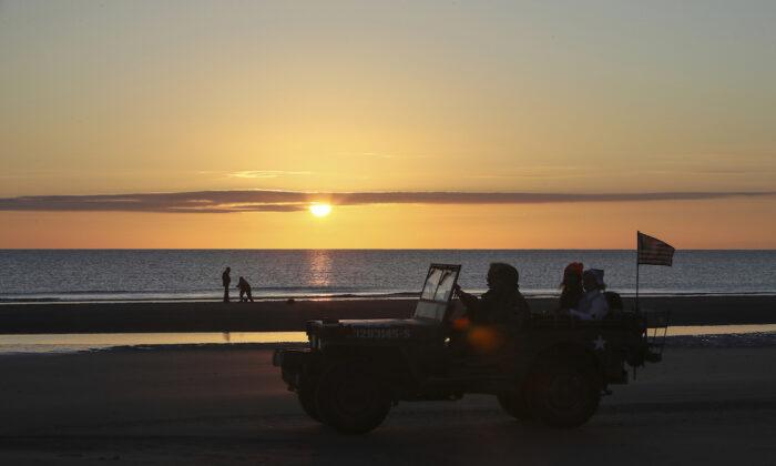 World War II reenactors drive a jeep at dawn on Omaha Beach in Saint-Laurent-sur-Mer, Normandy, France, on June 6, 2021. (David Vincent/AP Photo)