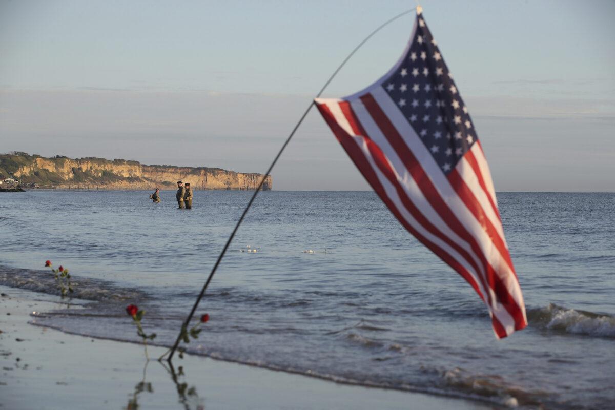 World War II reenactors stand in the sea on Omaha Beach