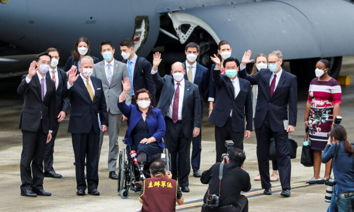 U.S. Sens. Tammy Duckworth (D-Ill.), Dan Sullivan (R-Alaska), and Chris Coons (D-Del.) wave next to Taiwan Foreign Minister Joseph Wu, and Brent Christensen, director of the American Institute in Taiwan, after their arrival via a U.S. Air Force freighter at Taipei Songshan Airport in Taipei, Taiwan, on June 6, 2021. (Central News Agency/Pool via Reuters)