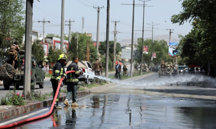 Afghan firefighters spray water at the scene of a roadside bomb explosion in Kabul, Afghanistan, on June 6, 2021. (Rahmat Gul/AP Photo)
