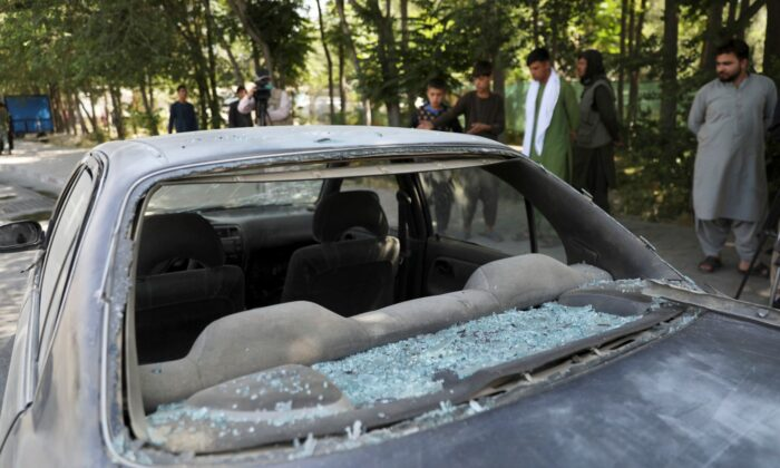 Afghan men look at a damage car after a roadside bomb explosion in Kabul, Afghanistan, on June 6, 2021. (Rahmat Gul/AP Photo)
