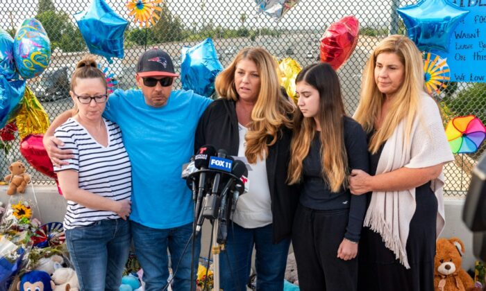 Family members of six-year-old Aiden Leos stand at a makeshift memorial on the Walnut Avenue overpass at the 55 Freeway in Orange, to announce that the reward for information leading to the suspects in the road-rage shooting death of Leos, Calif., on May 25, 2021. (Leonard Ortiz/File/The Orange County Register via AP)