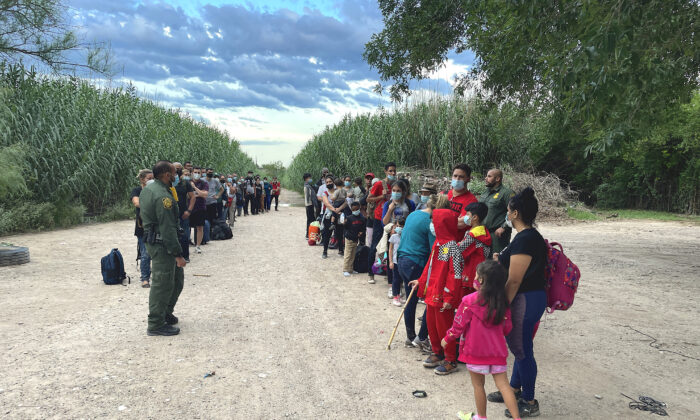 A group of Venezuelans wait to be picked up by Border Patrol after illegally crossing the Rio Grande from Mexico into Del Rio, Texas, on June 3, 2021. (Charlotte Cuthbertson/The Epoch Times)