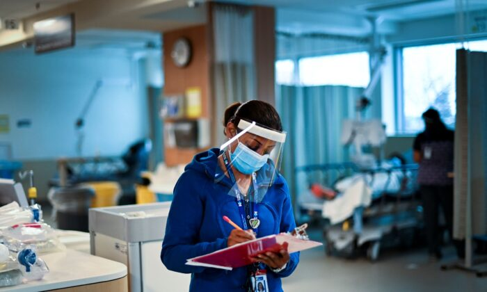 A health care worker audits different health units at a hospital in Toronto on Dec. 9, 2020. (The Canadian Press/Nathan Denette)