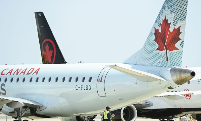 A worker walks past Air Canada planes grounded due to the pandemic on the tarmac at Pearson International Airport in Toronto on April 27, 2021. (The Canadian Press/Nathan Denette)