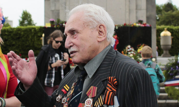Soviet war veteran David Dushman, 92, center, speaks to people holding Ukrainian flags as he attends a wreath laying ceremony at the Russian War Memorial in the Tiergarten district of Berlin, Germany, on  May 8, 2015. (Markus Schreiber/AP Photo)