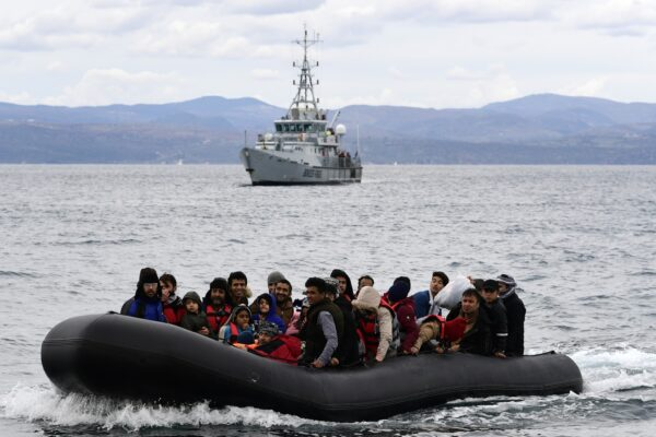 Refugees and migrants arrive in a dinghy accompanied by Frontex vessels