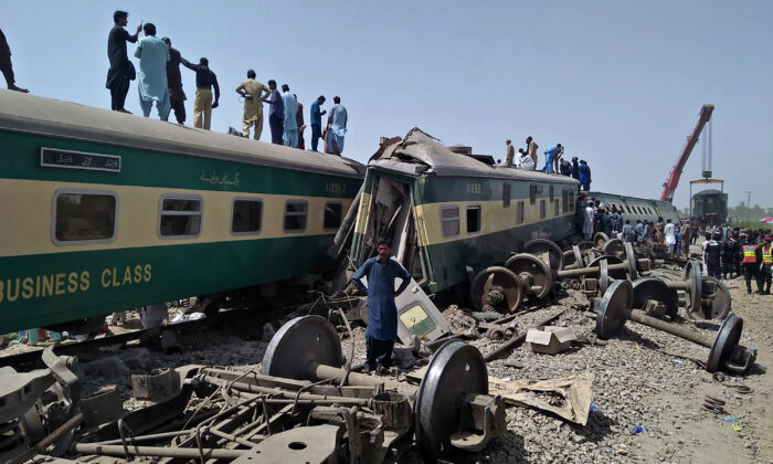 Pakistani volunteers and troops work at the site of trains collided in Ghotki district in the southern Pakistan, on June 7, 2021. (Waleed Saddique/AP Photo)