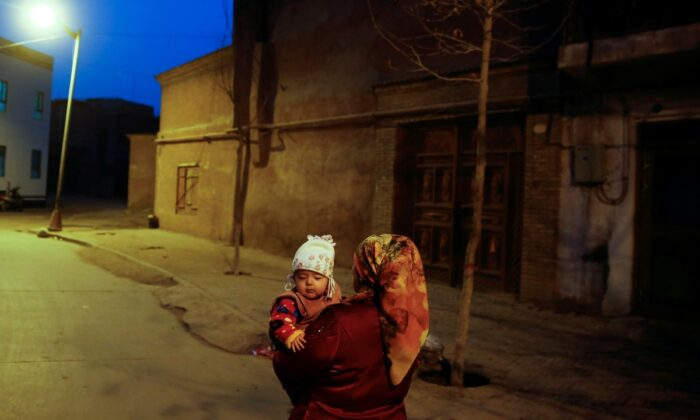 A woman carries a child at night in the old town of Kashgar, Xinjiang Uighur Autonomous Region, China, on March 23, 2017. (Thomas Peter/Reuters)