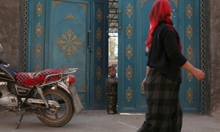 A child looks out from a door as a Uighur woman walks by in a residential area in Turpan, Xinjiang Uighur Autonomous Region, on Oct. 31, 2013. (Michael Martina/Reuters)