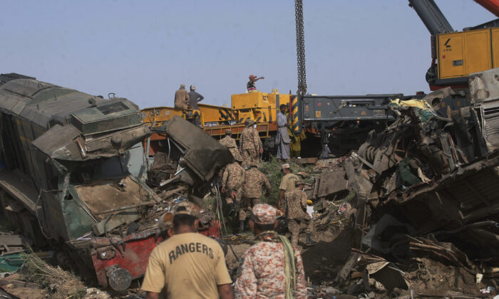 Soldiers arrive to conduct rescue operation to clear the track at the site of a train collision in the Ghotki district, southern Pakistan, on June 8, 2021. (Fareed Khan/AP Photo)